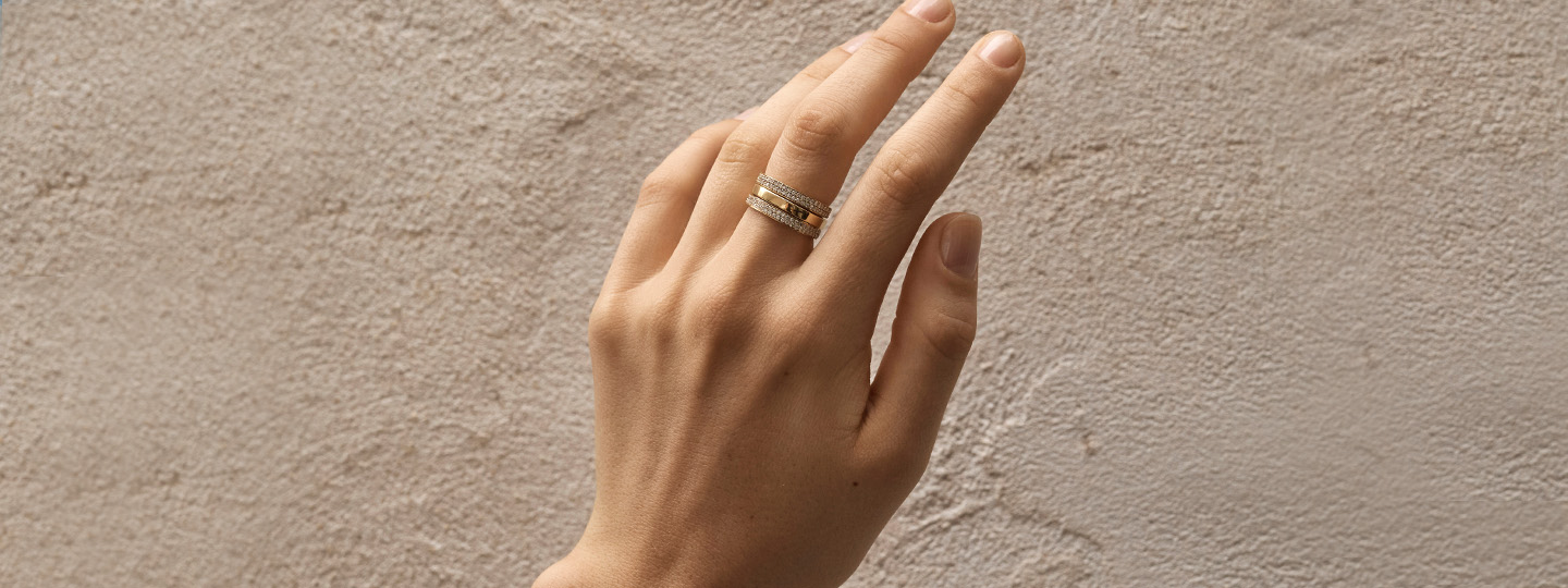 ring in yellow gold with diamonds from the magic collection by georg jensen on hand with beige background