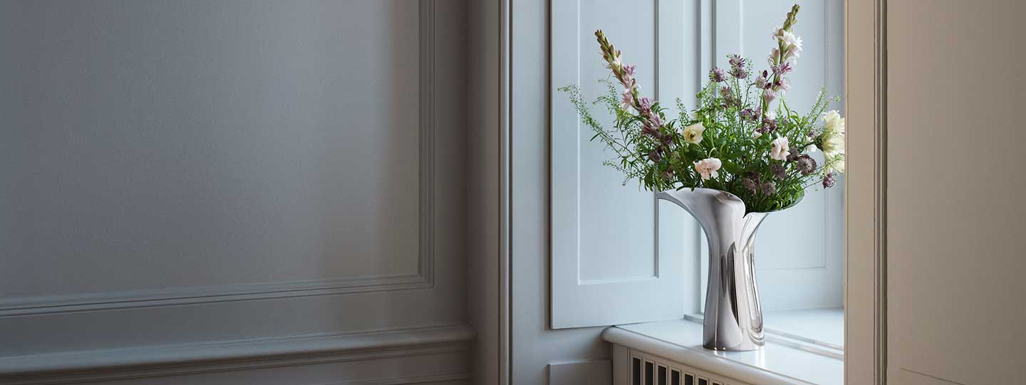 large vase in mirror polished stainless steel in a room from the Bloom Botanica collection by Georg Jensen