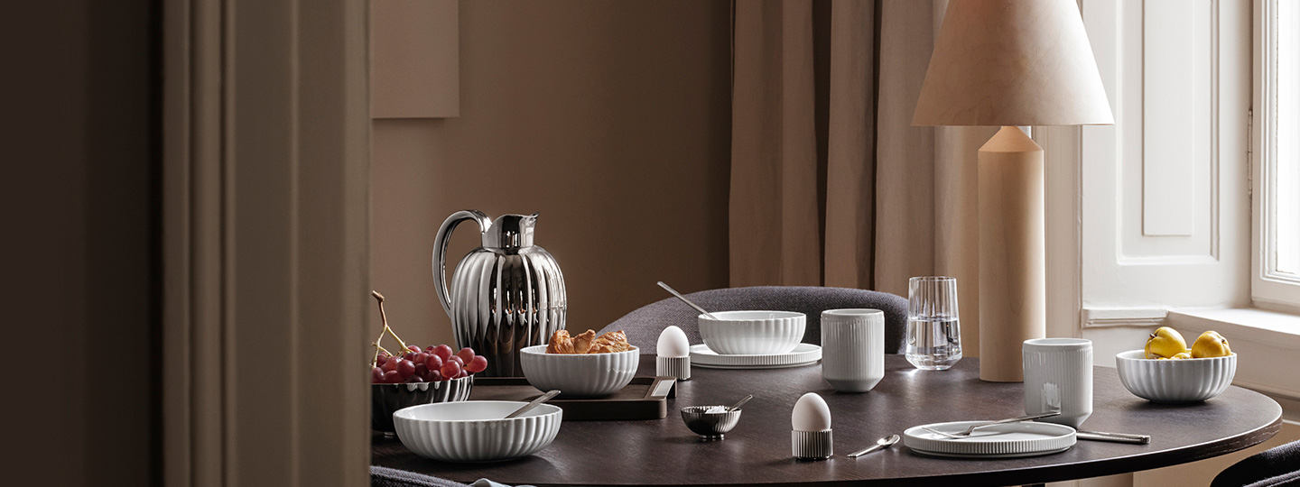 pitcher and cutlery in stainless steel and white porcelain bowls, plates and mugs on a table breakfast set up from the Bernadotte collection by Georg Jensen