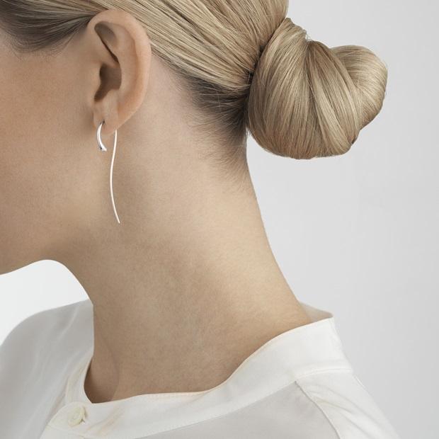 On model photo of sterling silver dangle earrings from Scandinavian jewellery brand Georg Jensen Mercy collection