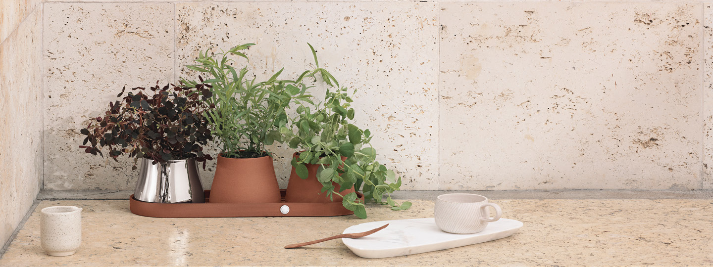 Pots and Planters from the Terra collection in terracotte and mirror polished stainless steel designed by swedish designer Snøhetta