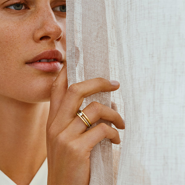 On model image of a ring in 18 kt. gold with diamonds from the Halo collection