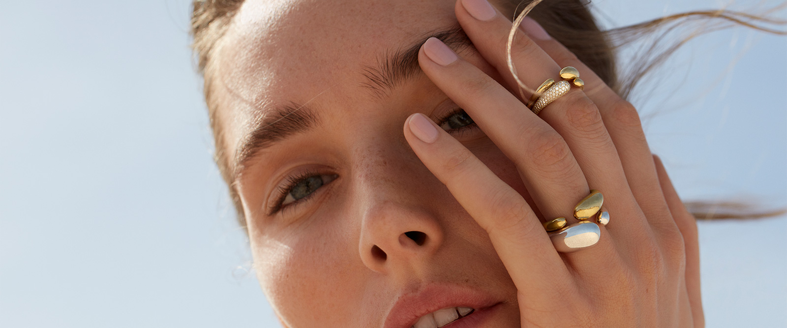 On model photo of Georg Jensen Mercy collection rings in 18kt yellow gold with diamonds and sterling silver