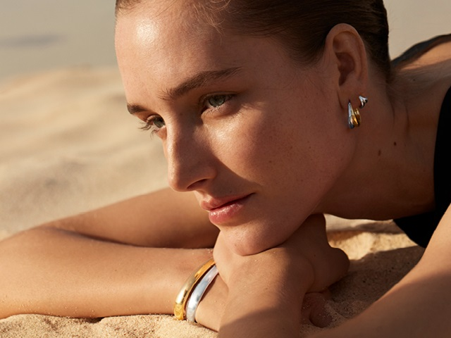 Georg Jensen on model photo of Curve collection sterling silver bangle and earrings in 18kt. Yellow gold and sterling silver