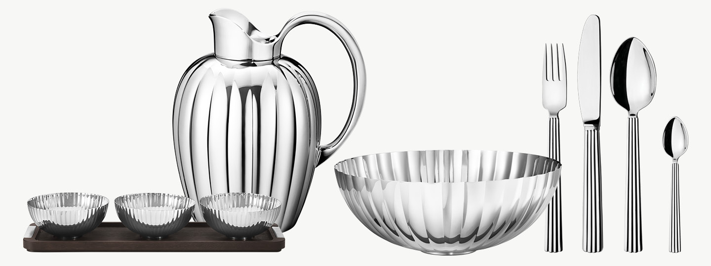Bowls, carafe and cutlery in mirror polished stainless steel from the Bernadotte collection