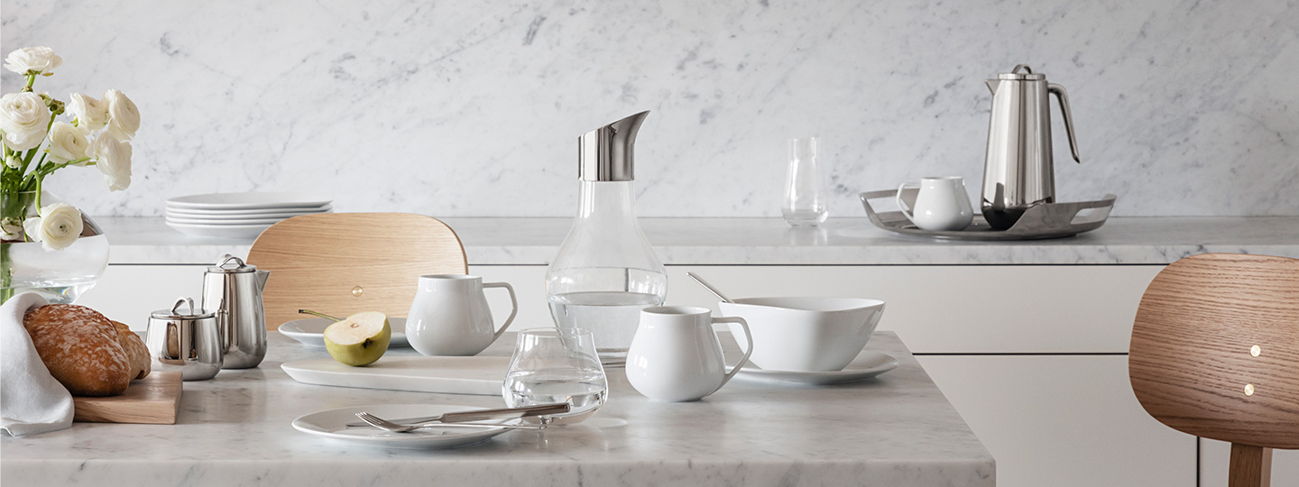 breakfast set up on a kitchen table featuring mug, bowl and plates in porcelain and pitcher in glass from the Sky collection and Helix thermo and milk jug and bowl in Mirror polished stainless steel