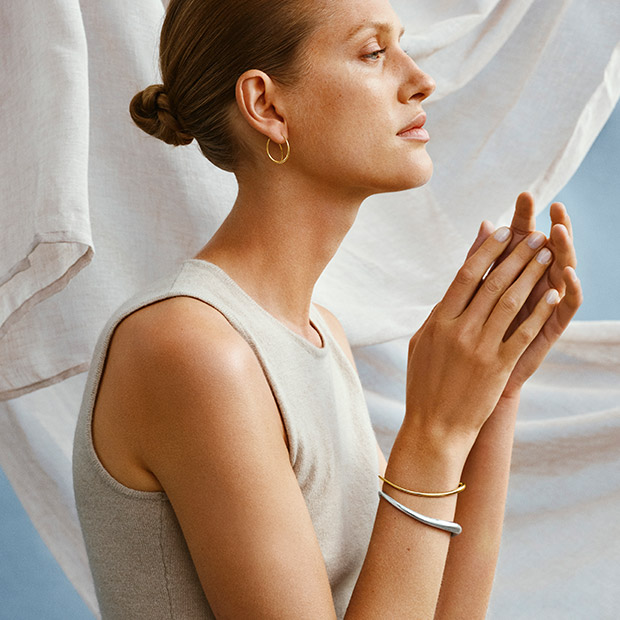 On model image with bracelets and earring in 18 kt. gold and Sterling Silver from the Offspring collection designed by Jacqueline Rabun