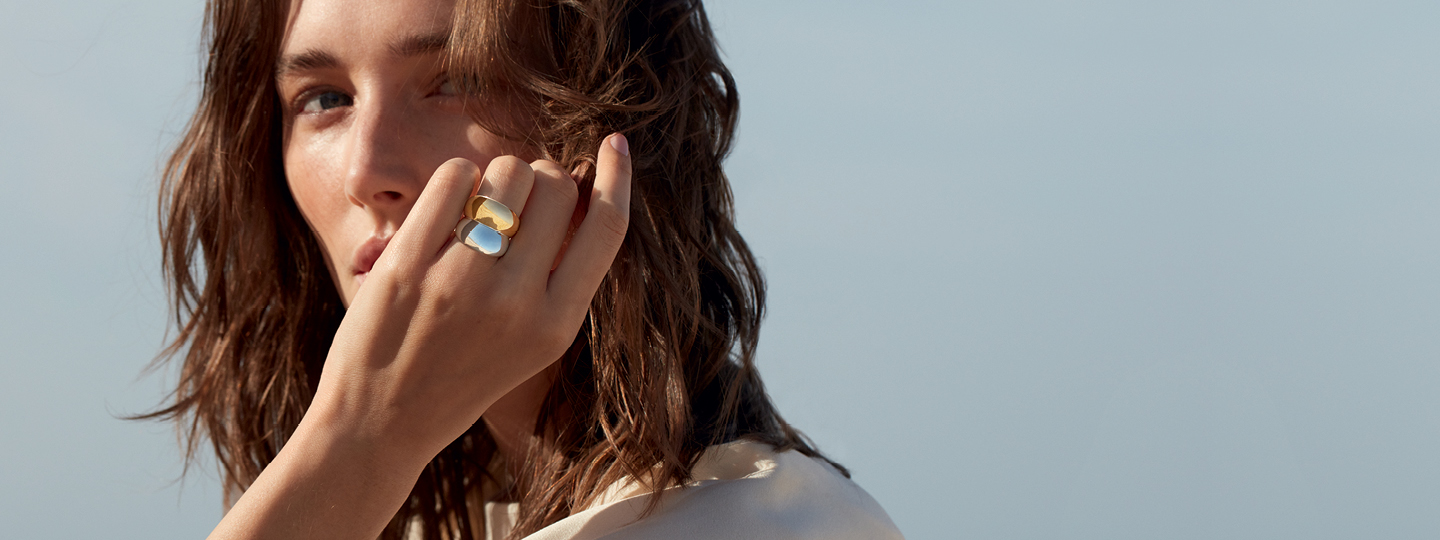 A photo of model wearing sterling silver and 18kt. Yellow gold ring from Georg Jensen Curve collection