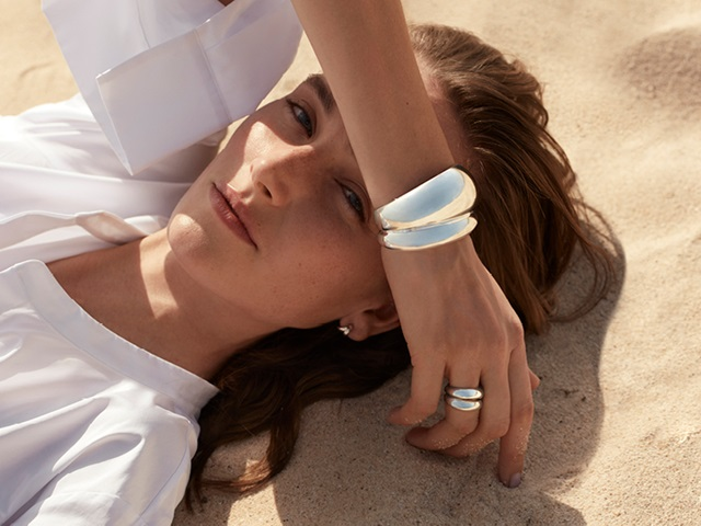 Georg Jensen on model photo of Curve collection sterling silver sculptural bangle designed by Regitze Overgaard