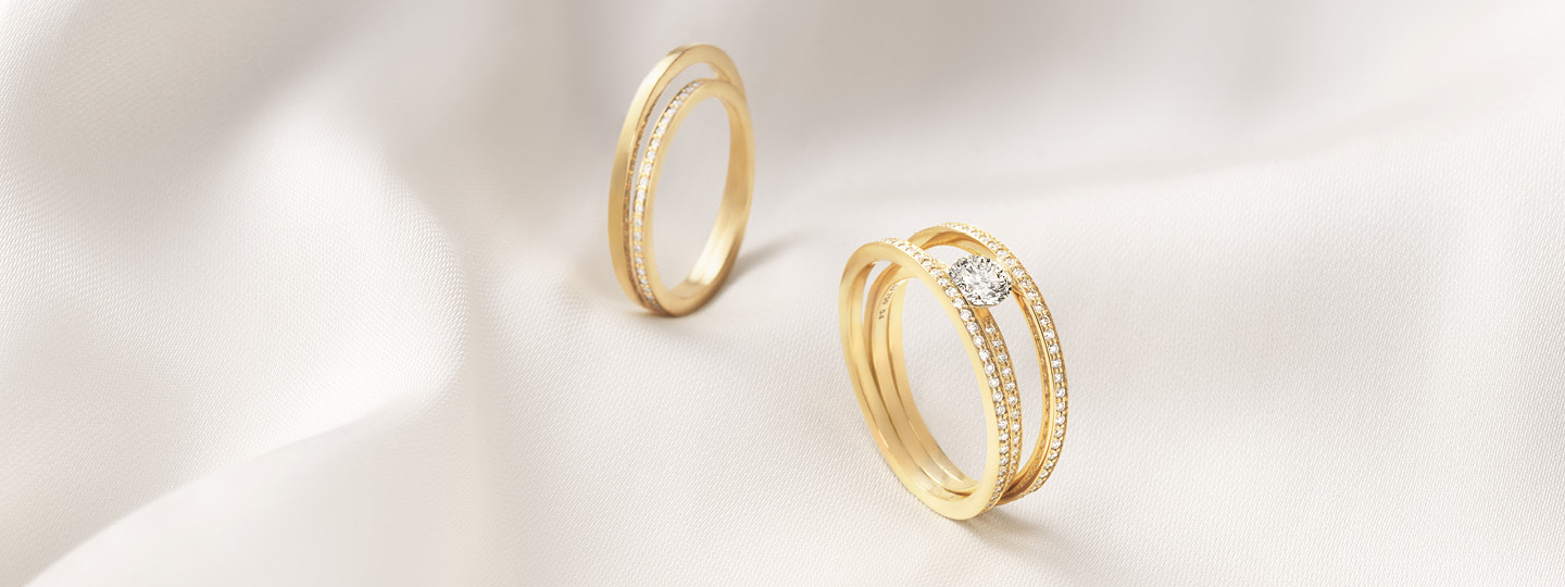 Halo solitaire ring and eternity ring from Georg Jensen in 18 karat gold and diamonfds